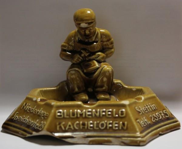 Auf dem Rand Aschenbecher in geschwungener Form sitzt die Figur eines Ofensetzers, der Kacheln behaut. Die umlaufenden 5 Felder sind beschriftet.