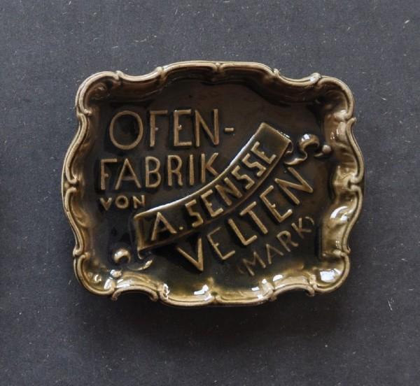 Der einfarbig olivbraun glasierte Aschenbecher mit Zierrand diente als Werbeträger für die Ofenfabrik Sensse. Der Firmenname erscheint mittig auf einer Banderole, um diese herum steht -Ofen-Fabrik von- und -Velten (Mark)-. Die Ofenfabrik von August Sensse wurde 1894 in der Kreisbahnstr. 7 gegründet und nach 1912 von der Familie seines Schwiegersohnes Hermann Hoffmann weitergeführt. Dieser Aschenbecher ist Teil der Sammlung von Souvenir- und Werbekeramiken in der Sammlung des Museums, die Beispiele sind für die Anstrengungen der Ofenfabrikanten, Aufmerksamkeit und Bekanntheit zu erhöhen.
