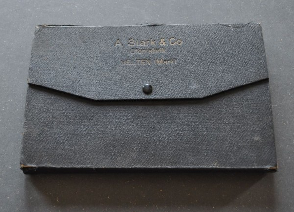 geschlossen - Die dreigliedrige schwarze Mappe aus Karton mit Deckel zeigt achtzehn Glasurmuster für Ofenkacheln. Auf jeder Musterkachel ist diagonal in der linken oberen Ecke das Firmenlogo eingeformt. Die Tonwarenfabrik August Stark & Co. wurde 1883 gegründet und produzierte sowohl Vasen als auch Kachelöfen.