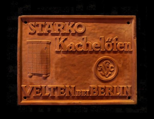 Tonplatte für Werbezwecke, links ein Kachelofen, rechts Firmenlogo im Kreis. Text: Starko Kachelöfen Velten bei Berlin.