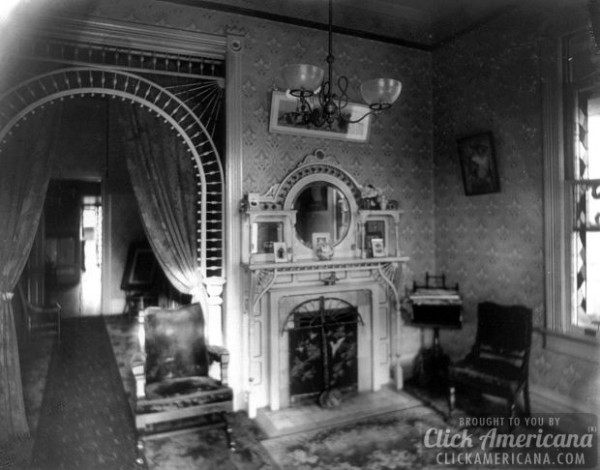 c1899-Interior-view-of-room-showing-chandelier-decorative-arch-fireplace-and-furniture